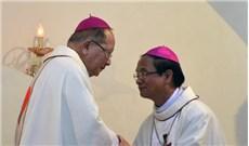 Đức cha Antôn Vũ Huy Chương đội mũ và đeo Thánh giá cho tân Giám mục